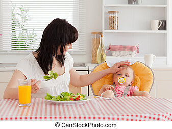 Gorgeous brunette woman eating a salad next to her baby while sitting in the kitchen