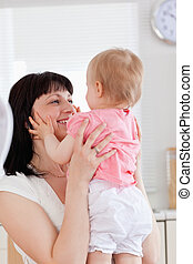 Gorgeous brunette woman holding her baby in her arms while sitting in the kitchen