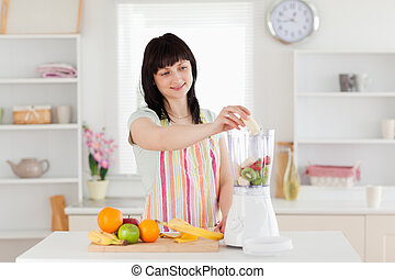 Gorgeous brunette woman putting vegetables in a mixer