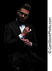 businessman wearing eyeglasses sitting and fixing his sleeve