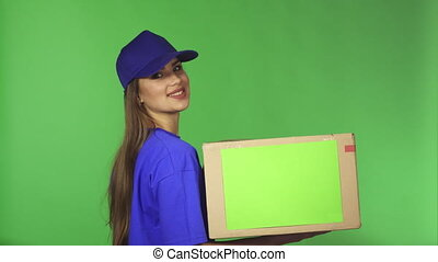 Gorgeous delivery service female agent showing thumns up holding cardboard box