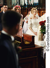 Gorgeous emotional blonde bride looking at handsome young groom in church