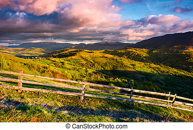 gorgeous evening in mountainous rural area. fence along the...