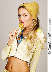 Gorgeous fashionable young woman holding a lemon candy