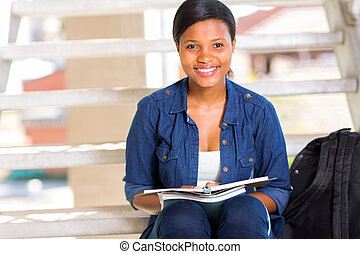 female african college student sitting on steps
