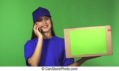 Gorgeous female delivery service worker delivering package talking on the phone
