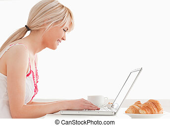 Gorgeous female having her breakfast while relaxing with a laptop