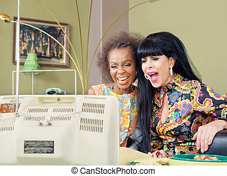 Gorgeous Female Pair Laughing at TV
