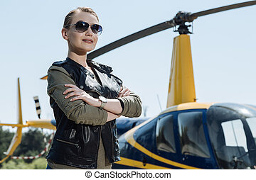 Gorgeous female pilot posing before taking helicopter ride