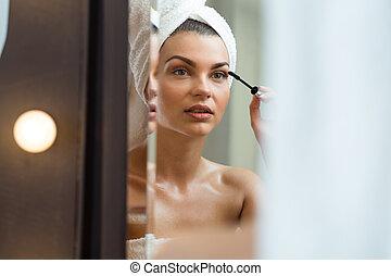 Gorgeous female putting makeup