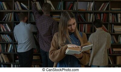 Gorgeous female student reading a book in library