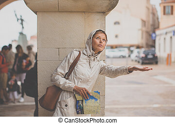 Gorgeous female tourist with a map discovering a foreign city