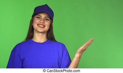 Gorgeous female worker in a baseball cap and t-shirt presenting copyspace