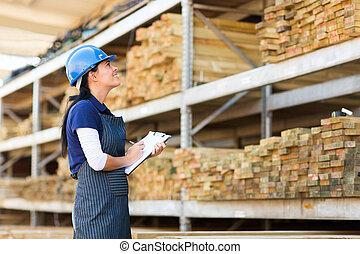 female worker stock taking in warehouse