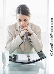 Gorgeous focused businesswoman reading her diary