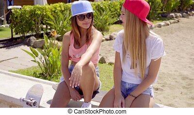 Gorgeous friends sitting on the beach with caps
