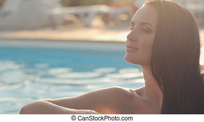 Gorgeous girl in the pool in sunshine