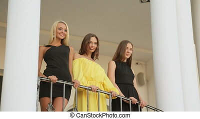 Gorgeous girls standing on the balcony