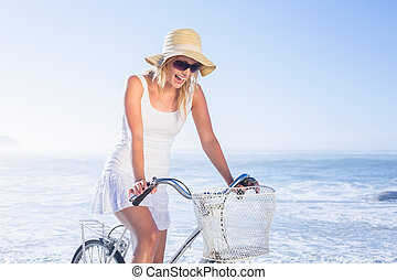 Gorgeous happy blonde on a bike ride at the beach on a sunny...