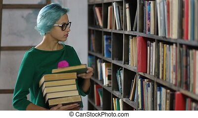 Gorgeous hipster girl in library looking for book -...