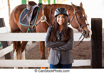 Pretty female Latin jockey wearing a jacket and a helmet standing next to a horse