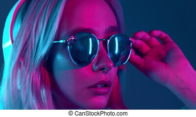Gorgeous lady with dyed hair and sunglasses listening music in headphones and singing with neon light background. Charming hipster girl dancing with eyes closed.