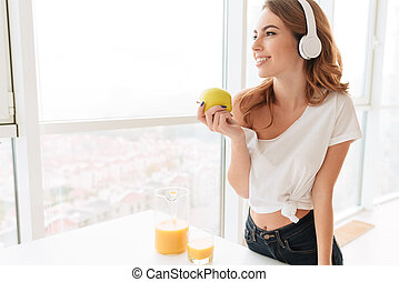 Gorgeous laughing young lady with headphones eating apple.