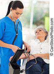medical doctor checking senior patient's blood pressure