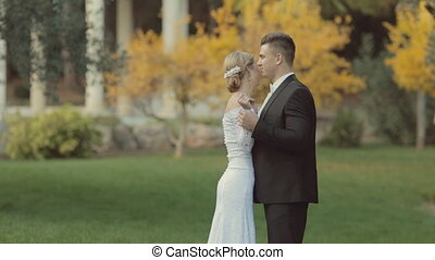 Gorgeous newlyweds fooling around and laughing in the park