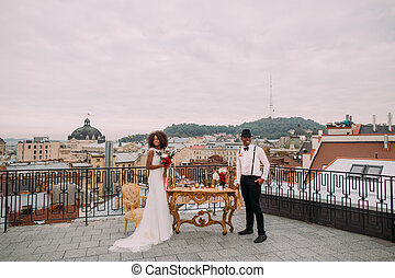 Gorgeous newlyweds on the terrace with amazing view on ancient Lviv architecture