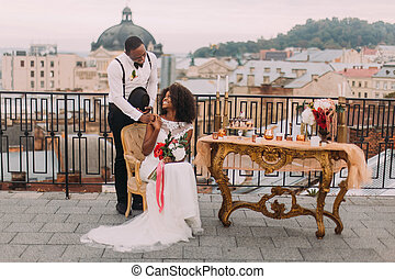 Gorgeous newlyweds softly holding hands on the terrace