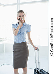 Gorgeous peaceful businesswoman phoning while standing in her office holding her suitcase