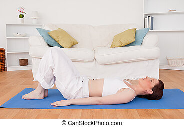 Gorgeous red-haired female stretching in the living room