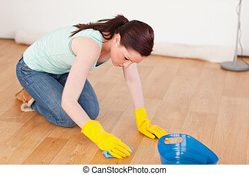 Gorgeous red-haired woman cleaning the floor while kneeling