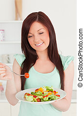 Gorgeous red-haired woman enjoying a mixed salad in the kitchen