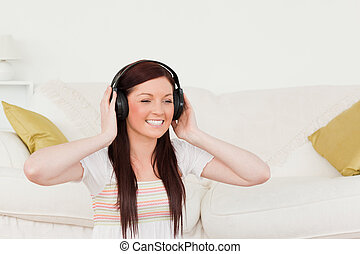 Gorgeous red-haired woman listening to music with headphones while sitting on a carpet in the living room