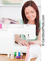 Gorgeous red-haired woman using a sewing machine in her living room