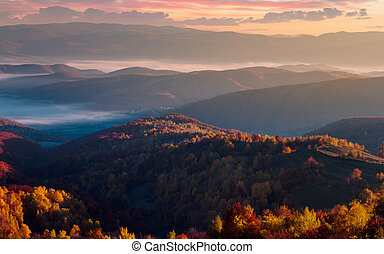 gorgeous red sunrise in mountains. forested hills in...
