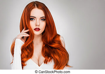 Gorgeous redhead girl with wavy hair beauty studio portrait