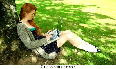 Gorgeous redhead typing on notebook leaning against tree in...