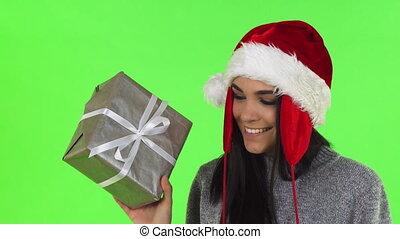 Gorgeous Santa Claus woman smiling holding Christmas gift