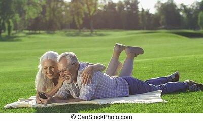 Gorgeous senior couple using mobile phone outdoors