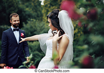 Gorgeous sexy brunette bride posing near rose bush with groom in the background