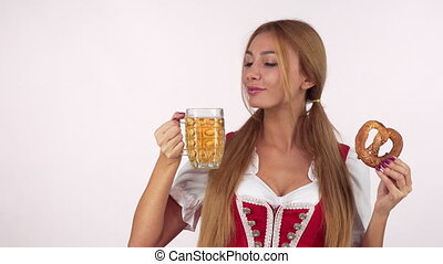 Gorgeous sexy German waitress in dirndl drinking beer,...