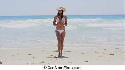 Gorgeous sexy young woman walking on a beach