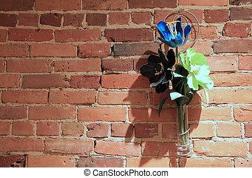 Gorgeous silk flowers on brick wall