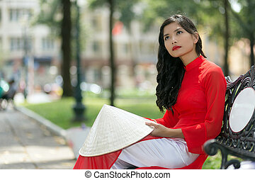 Gorgeous slender young Asian woman in red