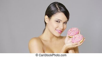 Gorgeous smiling woman holding donuts