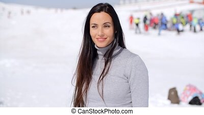 Gorgeous smiling young woman at a ski resort standing in the...