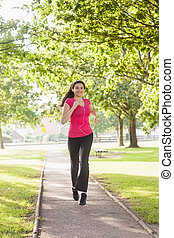 Gorgeous sporty woman jogging in a park
